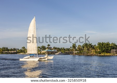 sailing boat in the canal in Fort Lauderdale in late afternoon without logos - stock photo