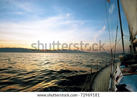 Sailing boat in the sea at sunset - stock photo