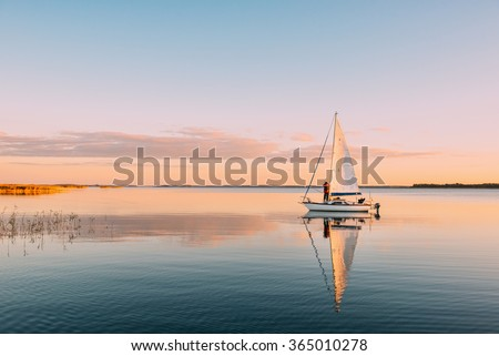 Sailing boat on a calm lake with reflection in the water. Serene scene landscape. Horizontal photograph. - stock photo