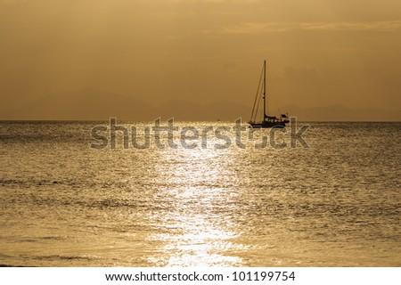 Sailing boat on beautiful sunset - stock photo
