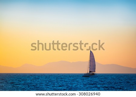 Sailing boat on the evening sea. Silhouette of far away mountains on the horizon