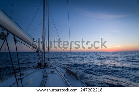 Sailing boat, open sea and sundown at the horizon - stock photo
