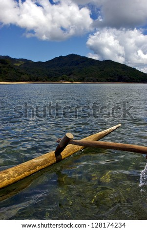 sailing boat palm  rock stone branch hill lagoon and coastline in madagascar nosy be