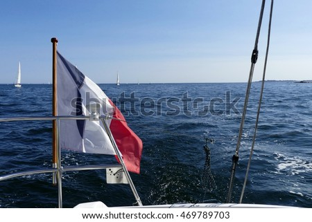 Sailing boat wake with french flag in the wind