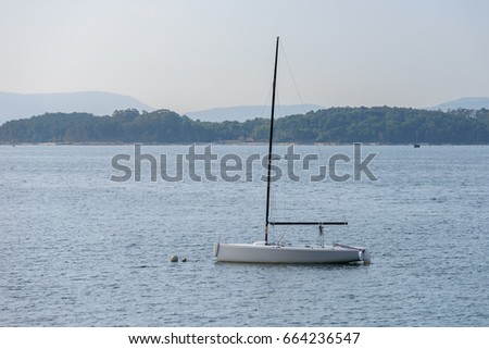 sailing boat with deflated sails moored near the shore