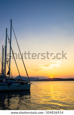 Sailing boats at sunset with Greek islands in the background