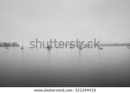 Sailing boats in fog on Lake Windermere in Lake District in black and white - stock photo