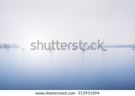 Sailing boats in fog on Lake Windermere in Lake District toned blue - stock photo