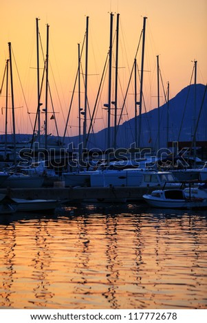 Sailing boats in marina at sunset - stock photo