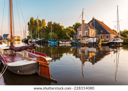 Sailing boats in the Dutch province of Friesland during sunset - stock photo