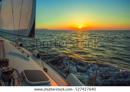 Sailing in the wind through the waves during sunset at the Aegean Sea in Greece. Luxury yachts.