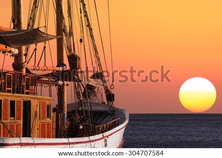 Sailing ship at sunset - stock photo