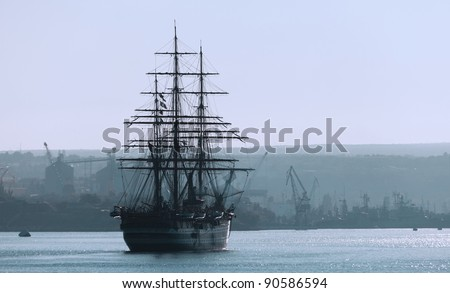 Sailing ship in the bay against the coastline - stock photo