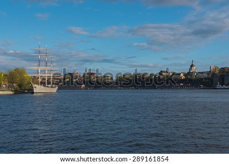 Sailing ship is in foreground of old town at evening, Stockholm, Sweden.