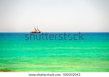 Sailing ship on horizon of azure sea