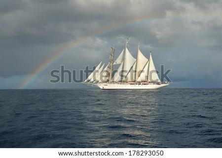 Sailing ship on the background of rainbow - stock photo