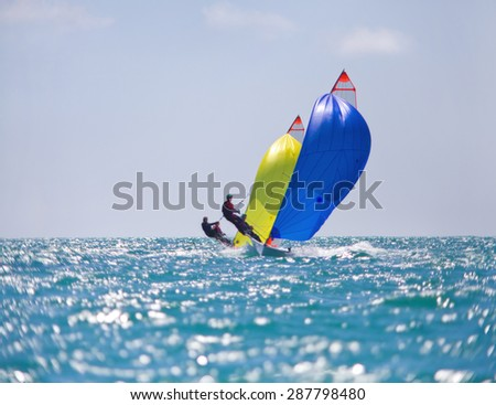 Sailing ship yachts with colored sails in a row - stock photo