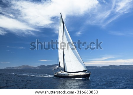 Sailing ship yachts with white sails in the Sea. Luxury boats. - stock photo