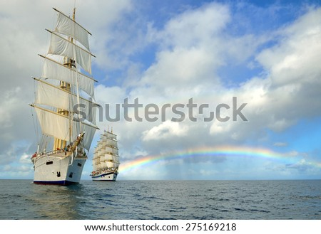 Sailing ships and a beautiful rainbow in the sea - stock photo