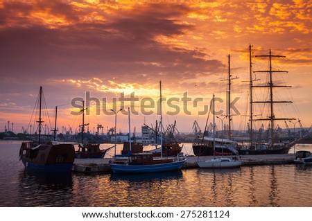 Sailing ships and yachts stand moored in Varna harbor at the sunset. Black Sea coast, Bulgaria - stock photo