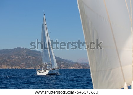 Sailing ships yachts with white sails in the open sea.