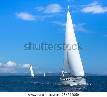 Sailing ships yachts with white sails in the open sea. Sailing yacht race.  - stock photo