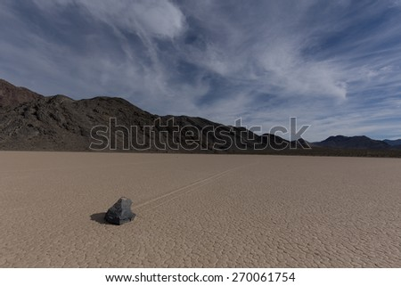 Sailing Stone on a cracked dry lake floor with blue sky obscured by clouds and mountains on background at the Racetrack Playa in Death Valley National Park, California - stock photo