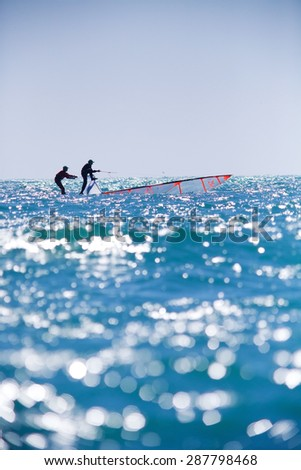 sailing team fighting to save the ship from overturn in sea - stock photo