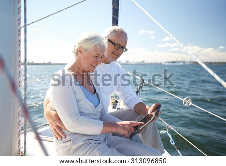 sailing, technology, tourism, travel and people concept - happy senior couple with tablet pc computer on sail boat or yacht deck floating in sea - stock photo