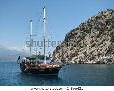 Sailing vessel with a having a rest girls not far from mountain - stock photo