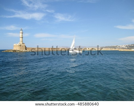 Sailing White Yacht near the Lighthouse at the Old Venetian Harbour of Chania, Crete Island, Greece