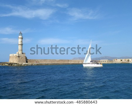 Sailing White Yacht near the Lighthouse on the Blue Aegean Sea, Crete Island, Greece