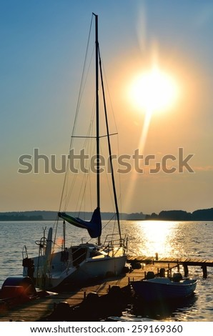 Sailing yacht and jetty. Empty wooden jetty with moored boats on the lake shore at the sunrise in Mazury region, Poland.  - stock photo
