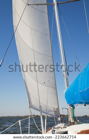 Sailing yacht catches the wind. View on deck of sailing yacht. Picture from perspective of sitting on deck of yacht.