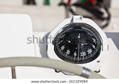 Sailing yacht compass and control wheel. Horizontal close up shot - stock photo
