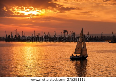 Sailing yacht enters Varna harbor at the sunset. Black Sea, Bulgaria - stock photo