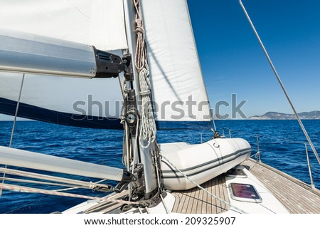 Sailing yacht going on her sails in calm weather with dinghy on board