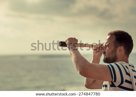 Sailor man looking through the binoculars against blue sky background - stock photo