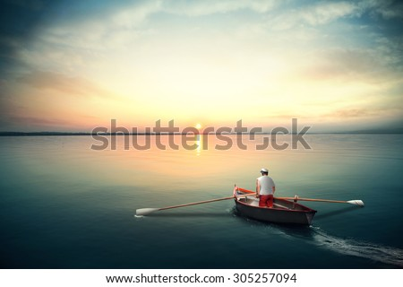 Sailor on a canoe rowing on the calm water - stock photo