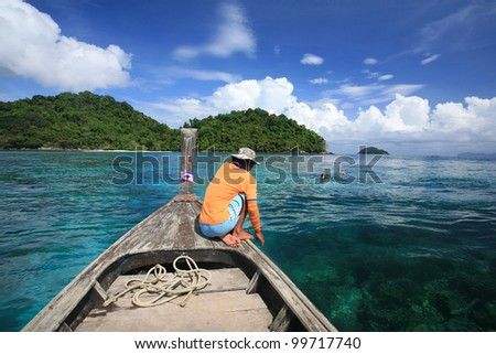 Sailor on wooden boat waiting visitors snorkeling to see coral reef on blue andaman sea at Surin islands national park, Thailand - stock photo