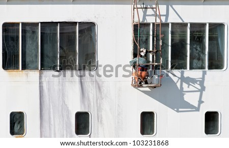 Sailor painting the hull of the huge ferry - stock photo