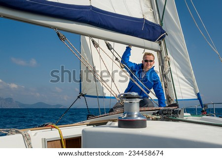Sailor stays at his yacht, witch is going on the sea on full sails. - stock photo