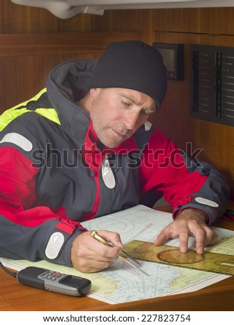 Sailor studying navigation chart of coastal area - stock photo