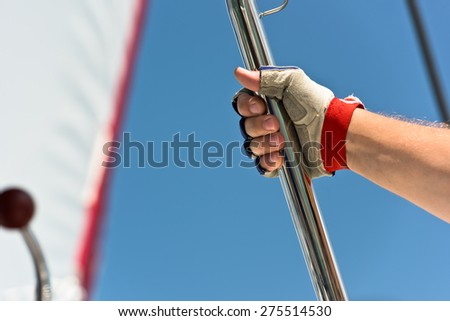 Sailors hand on a sailboat. Shot with a selective focus - stock photo