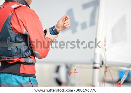 Sailors in action with sailing boat on regatta ocean marina background - stock photo