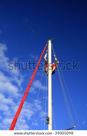 Sailors on a sunny day repair yacht mast - stock photo