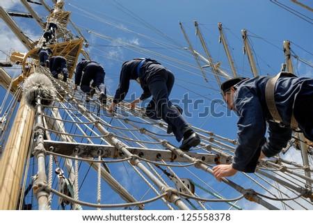 Sailors sailing ship are raised at the  mast - stock photo
