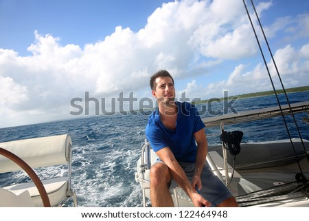 Sailot pulling on sail rope during navigation - stock photo