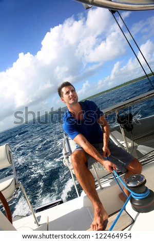 Sailot pulling on sail rope during navigation - stock photo