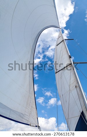 Sails filled with wind against the sky with clouds. Wind greatly inflated sails and mast tilt. Bottom view of the sails, mast and blue sky with clouds. Clear summer day. - stock photo